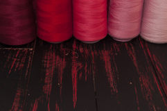Spools of thread in red scale sewing Royalty Free Stock Image
