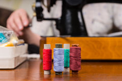 Spools of Thread on Table by Sewing Machine Stock Image