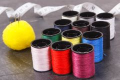 Spools of thread, tape measure and needle. Accessories for embroidery and sewing. Spools of colorful thread, tape measure and needle. Accessories for sewing royalty free stock photo