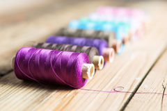 Spools of thread on wooden  background. Old sewing accessories. Royalty Free Stock Image