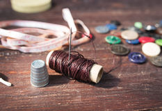 Spools of threads and buttons on old wood Stock Images