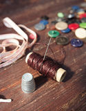 Spools of threads and buttons on old wood Royalty Free Stock Photos