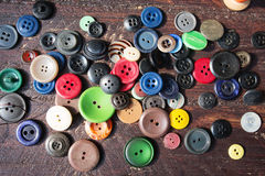 Spools of threads and buttons on old wood Stock Photo