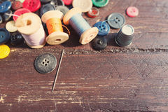 Spools of threads and buttons on old wood Royalty Free Stock Image