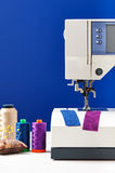 Spools of threads next to sewing machine on deep blue background Royalty Free Stock Photo