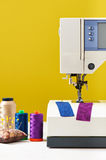 Spools of threads next to sewing machine on yellow background Royalty Free Stock Photo