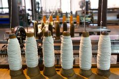 Spools of yarn with old spinning machine Stock Photo