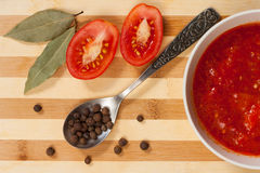 Spoon With Allspice, Bay Leaf, Fresh Tomato Cut In Half And Tom. Metal Spoon With Allspice, Bay Leaf, Fresh Tomatoes And Tomato Sauce On Wooden Table, Top View royalty free stock photos