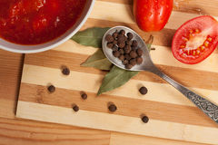 Spoon With Allspice, Bay Leaf, Fresh Tomatoes And Tomato Sauce. Metal Spoon With Allspice, Bay Leaf, Fresh Tomatoes And Tomato Sauce On Wooden Table, Close Up royalty free stock photography