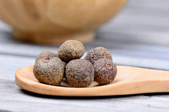 Spoon with allspice on table. Spoon with allspice on wooden table royalty free stock photography