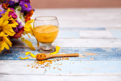 Spoon with bee pollen and liquid pollen in glass. On the table royalty free stock photography