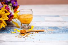 Spoon with bee pollen and liquid pollen in glass. On the table royalty free stock image