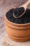 Spoon with black sturgeon caviar. In a wooden keg on the table. macro. vertical Royalty Free Stock Image