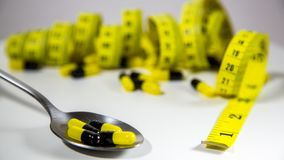 Spoon with pills and measuring tape to represent the diet pill industry. Spoon with black and yellow pills and measuring tape on white background to represent royalty free stock image