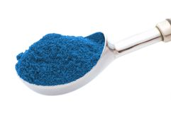 Spoon with blue powder. Silver spoon with blue powder isolated on white Stock Photo