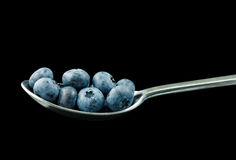 Spoon with blueberries against a black background Royalty Free Stock Photography