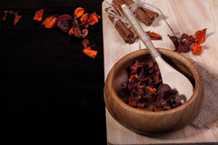 Spoon and bowl. Wooden spoon and bowl with bundles of cinnamon on a wooden surface royalty free stock photos