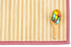 Spoon with capsule pills on mat Stock Photo