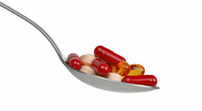 Spoon with capsules Royalty Free Stock Photography