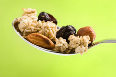 Spoon with cereal, nuts and raisin Royalty Free Stock Image