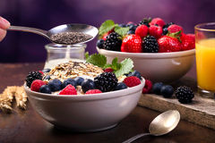 Spoon of chia and some berries. Spoon of chia. Flavoring oatmeal with white yoghurt and some berries. Cup of fresh orange juice royalty free stock photo