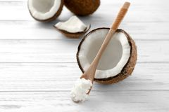 Spoon with coconut oil and nut. On wooden table Stock Photos