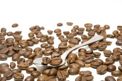 Spoon with coffee beans. Randomly disposed isolated in white background Stock Images