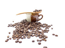 Spoon of coffee beans on a cup isolated (selective focusing at spoon) Stock Images