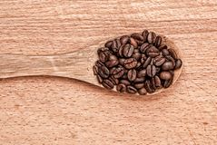 Spoon with  coffee beans on a wooden table Royalty Free Stock Image