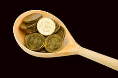 Spoon with coins on a black background Stock Photography