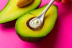 Spoon of cosmetic cream in cut avocado on a bright background. The concept of skin care, self-care, natural cosmetics royalty free stock photography