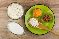 Spoon with cottage cheese, raisins and dried apricots, yogurt. Spoon with cottage cheese, raisins and dried apricots in plate, yogurt on wooden table. Top view Royalty Free Stock Images