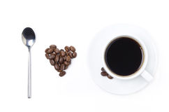 Spoon, cup of black coffee and coffee beans in the form of heart Stock Image