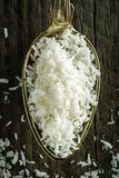 Spoon of desiccated coconut flakes on a wooden background Stock Image