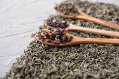 Spoon and different types of dry tea on table stock photography