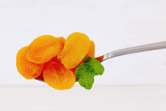 Spoon of dried apricots Stock Images