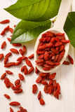 Spoon of dried goji berries, wooden background Stock Photo