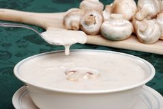 Spoon dripping cream of mushroom soup Stock Images