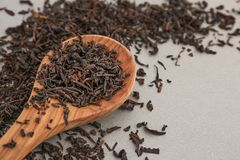 Spoon with dry black tea leaves on grey background stock images