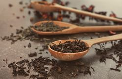 Spoon with dry black tea leaves on table stock photo
