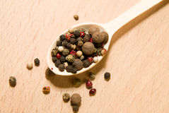 Spoon filled with grains of pepper  on a wooden surface Stock Images
