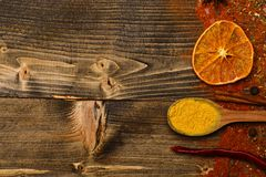 Spoon filled with kitchen herbs, red pepper and curcuma lay on wooden background, copy space. Condiments scattered all. Over surface. Condiments concept. Spices stock photography
