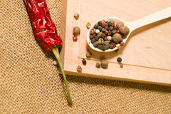 Spoon filled with a mixture of grains of pepper are on a wooden Stock Image