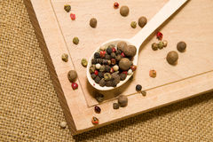 Spoon filled with a mixture of grains of pepper are on a wooden Stock Photography