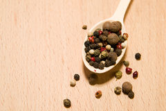 Spoon filled with a mixture of grains of pepper are on a wooden Stock Photo