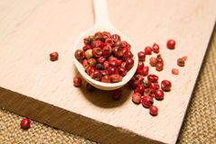 Spoon filled with a mixture of grains of pepper are on a wooden Royalty Free Stock Photos