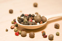 Spoon filled with a mixture of grains of pepper are on a wooden Stock Images