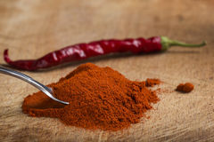 Spoon filled with red hot paprika powder and one dried chilli Royalty Free Stock Image