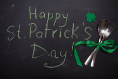 Spoon and fork on blackboard with words Happy St. Patricks Day Stock Image