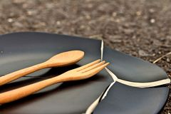 Spoon and fork on a crack  black plate. Stock Images